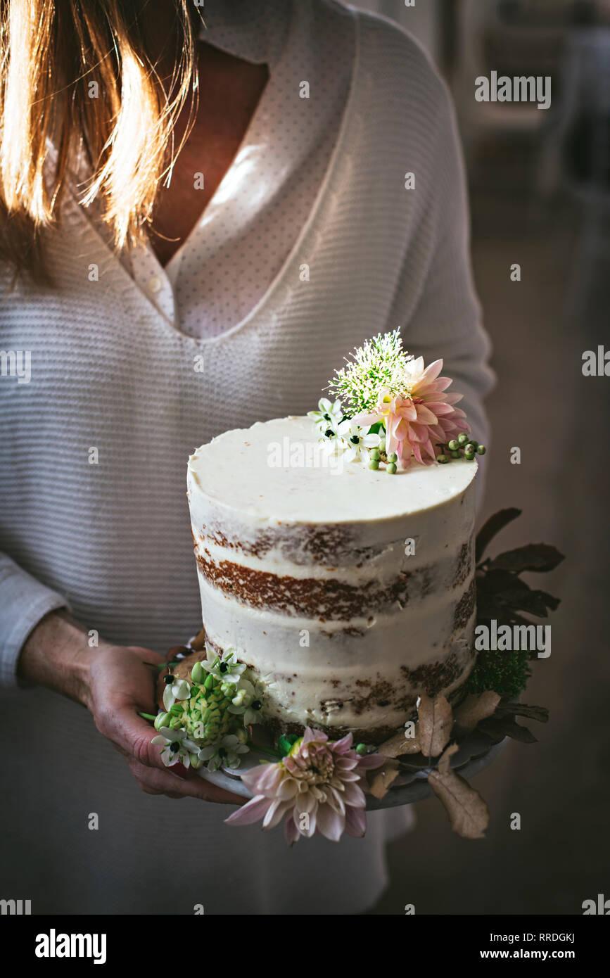 Seitenansicht des Ernteguts glücklich Frau Teller mit leckeren Kuchen von chrysantheme Bud und trockene Blätter im Zimmer eingerichtet Stockbild