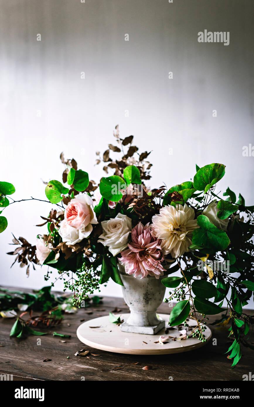 Konzept der Blumenstrauß der trockene und frische Rosen, Chrysanthemen und Pflanze Zweige im Retro-look Vase auf Holzbrett auf grauem Hintergrund Stockbild