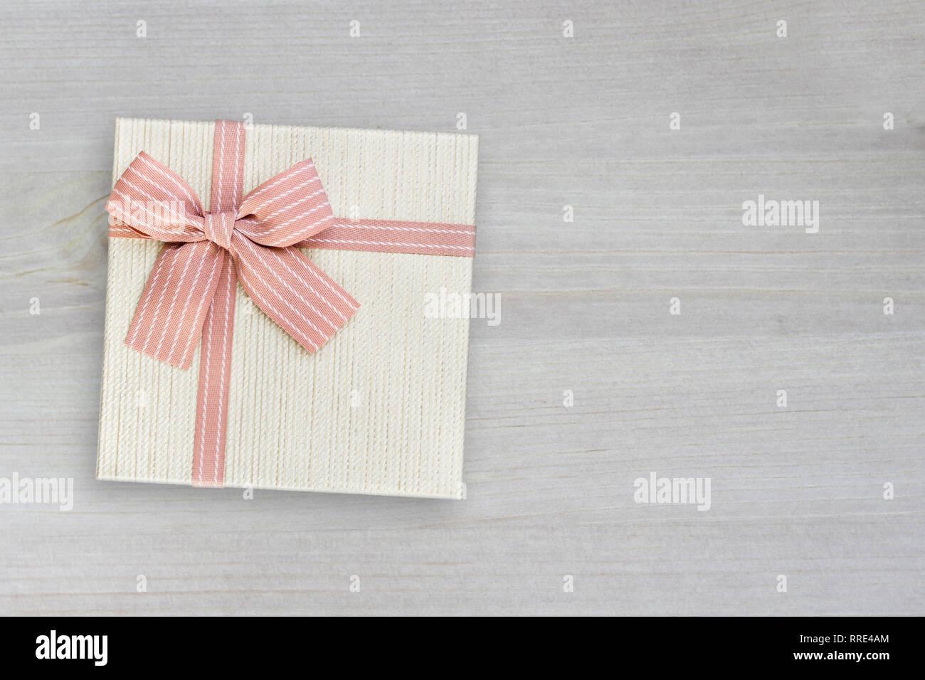 Geschenkkarton Weihnachten.Beige Geschenkkarton Mit Pink Ribbon Auf Holz Hintergrund