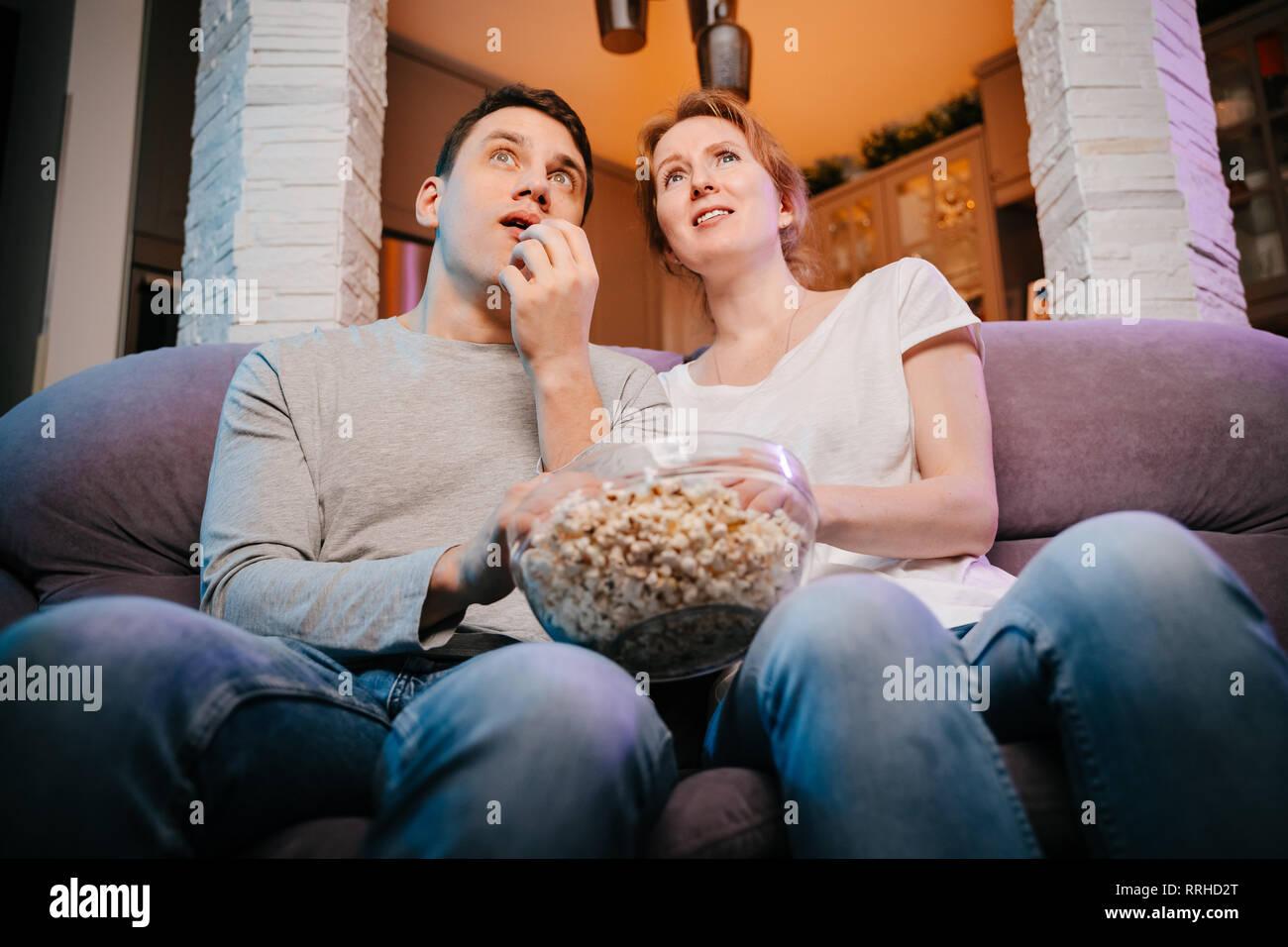 Junges Paar essen Popcorn und einen Film zu Hause auf der Couch, Angst. Stockbild