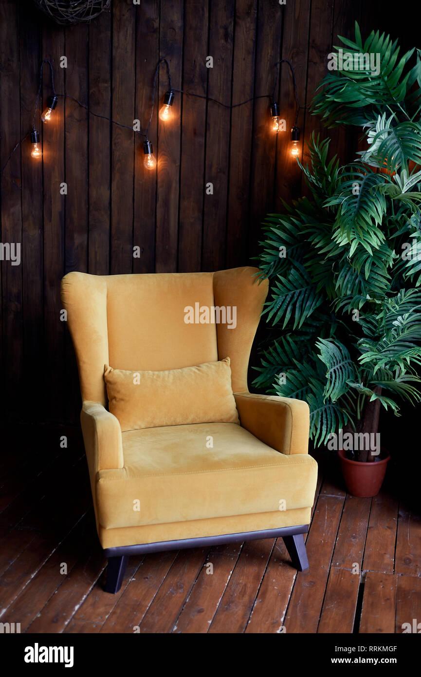 Gemütliche alte senffarbenen Sessel, Palme und Holzwände. Innenbereich im Retro Style. Warme Gelb Girlande Licht. Stockbild