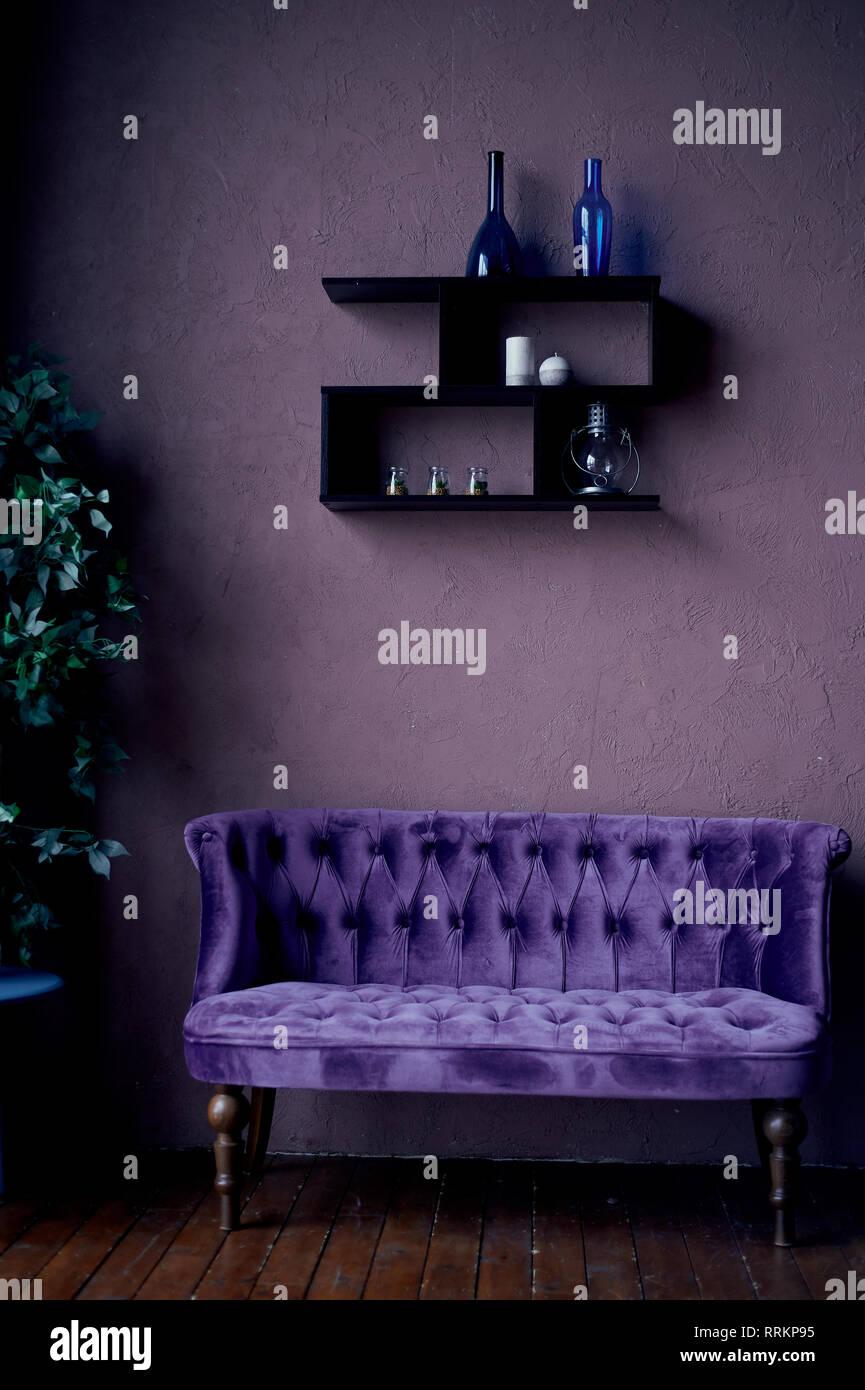 Retro Interieur mit purpurroten Sofa und dunklen Wänden. farbigen Flaschen. Geistiges Haus Stockfoto