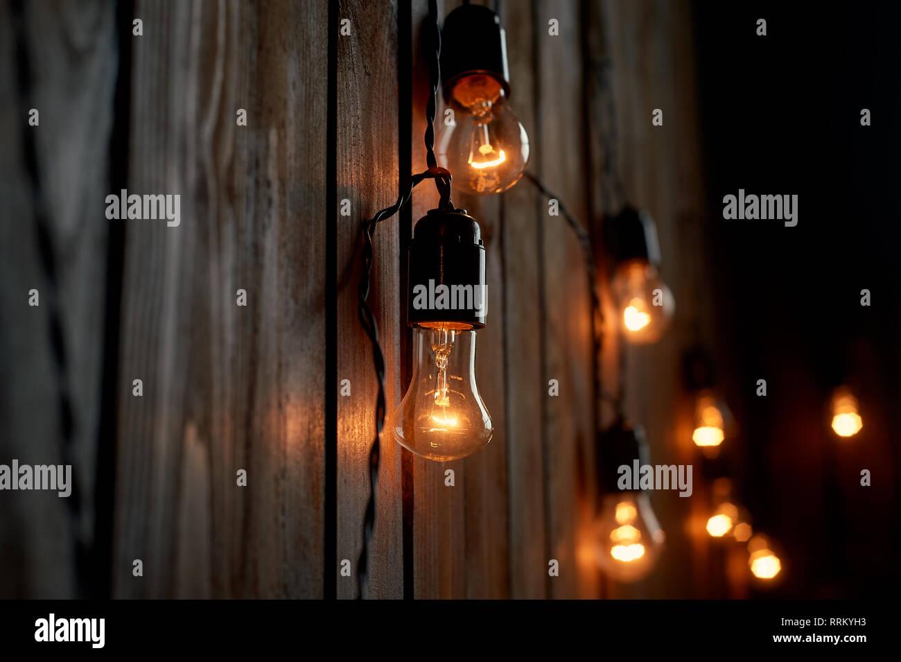 Edison Glühlampe hängt an einem langen Draht. Gemütliche warme gelbe Licht. Retro Stockbild
