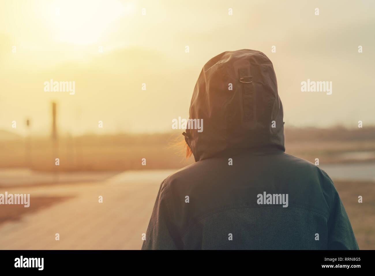 Ansicht der Rückseite mit Kapuze weibliche Person zu Fuß die Stadt Straße im kalten Winter am Nachmittag Stockfoto