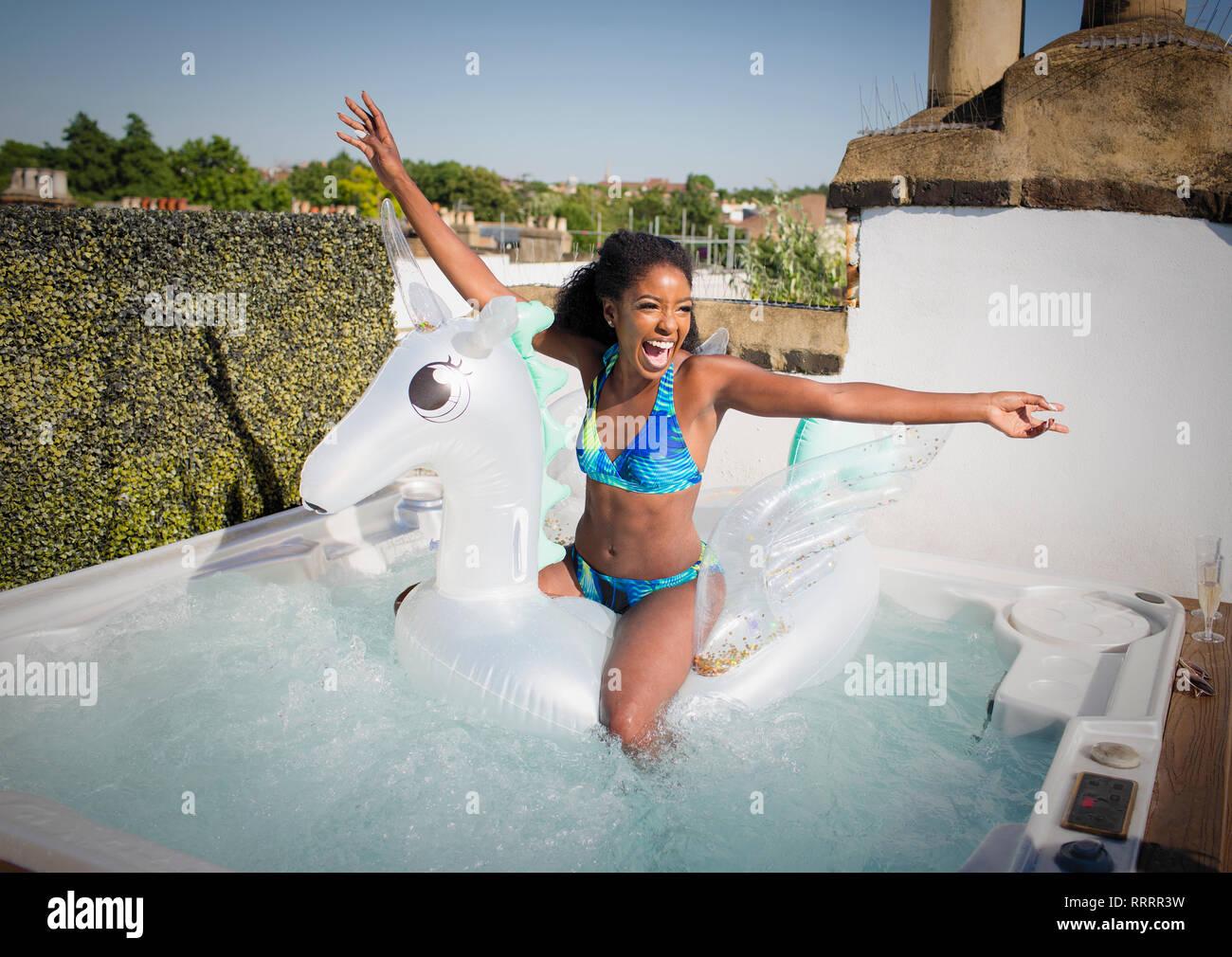Verspielt, quirlige junge Frau im Bikini sitzt n aufblasbare Pegasus im Whirlpool auf dem Dach Stockbild