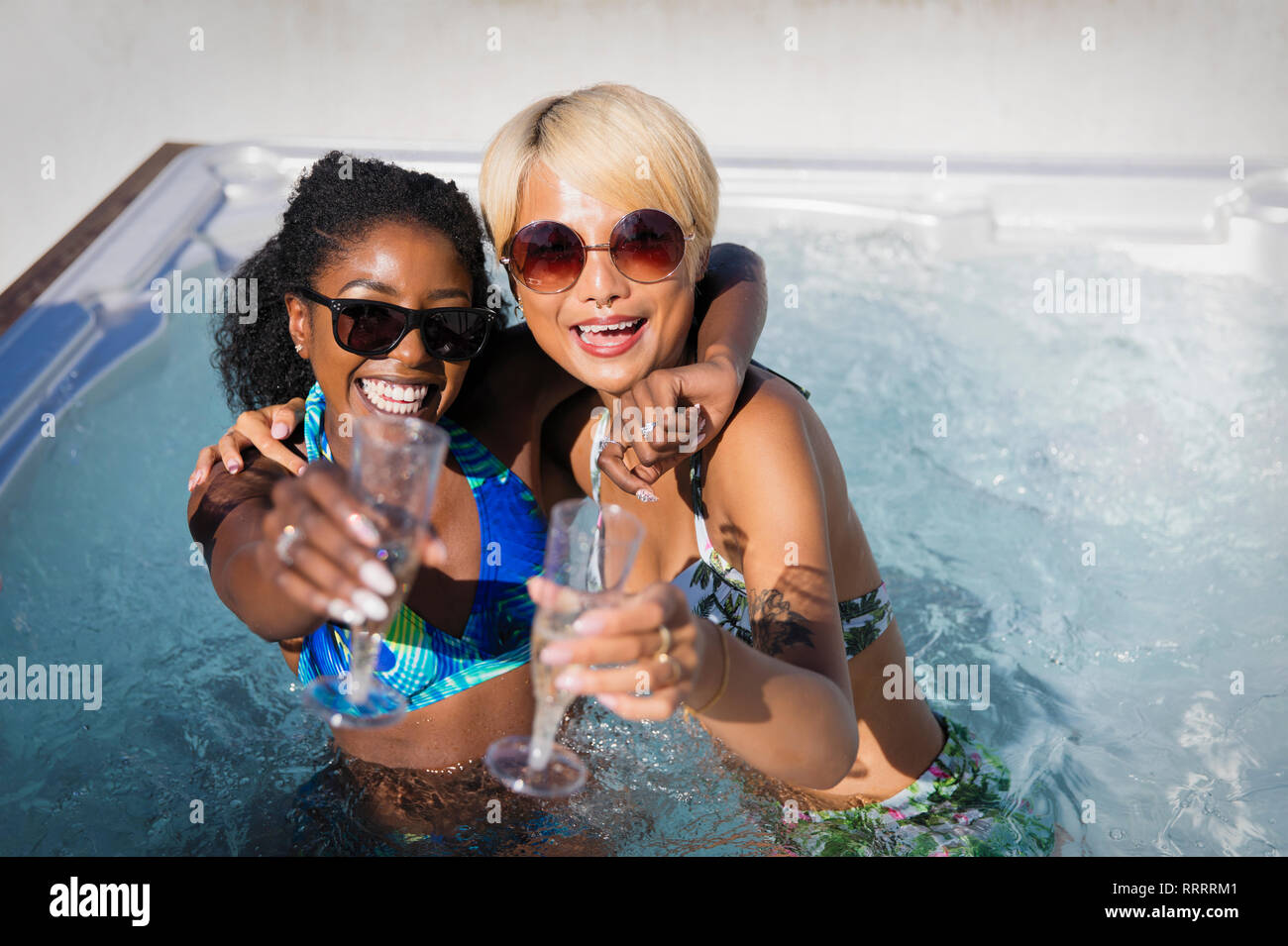 Portrait ausgelassenen jungen Frauen Freunde trinken Champagner im sonnigen Whirlpool Stockbild