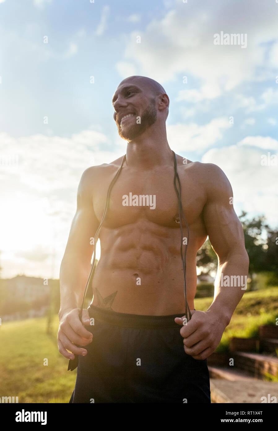 Portrait von lächelnden barechested muskulösen Mann mit Springseil im Freien Stockbild