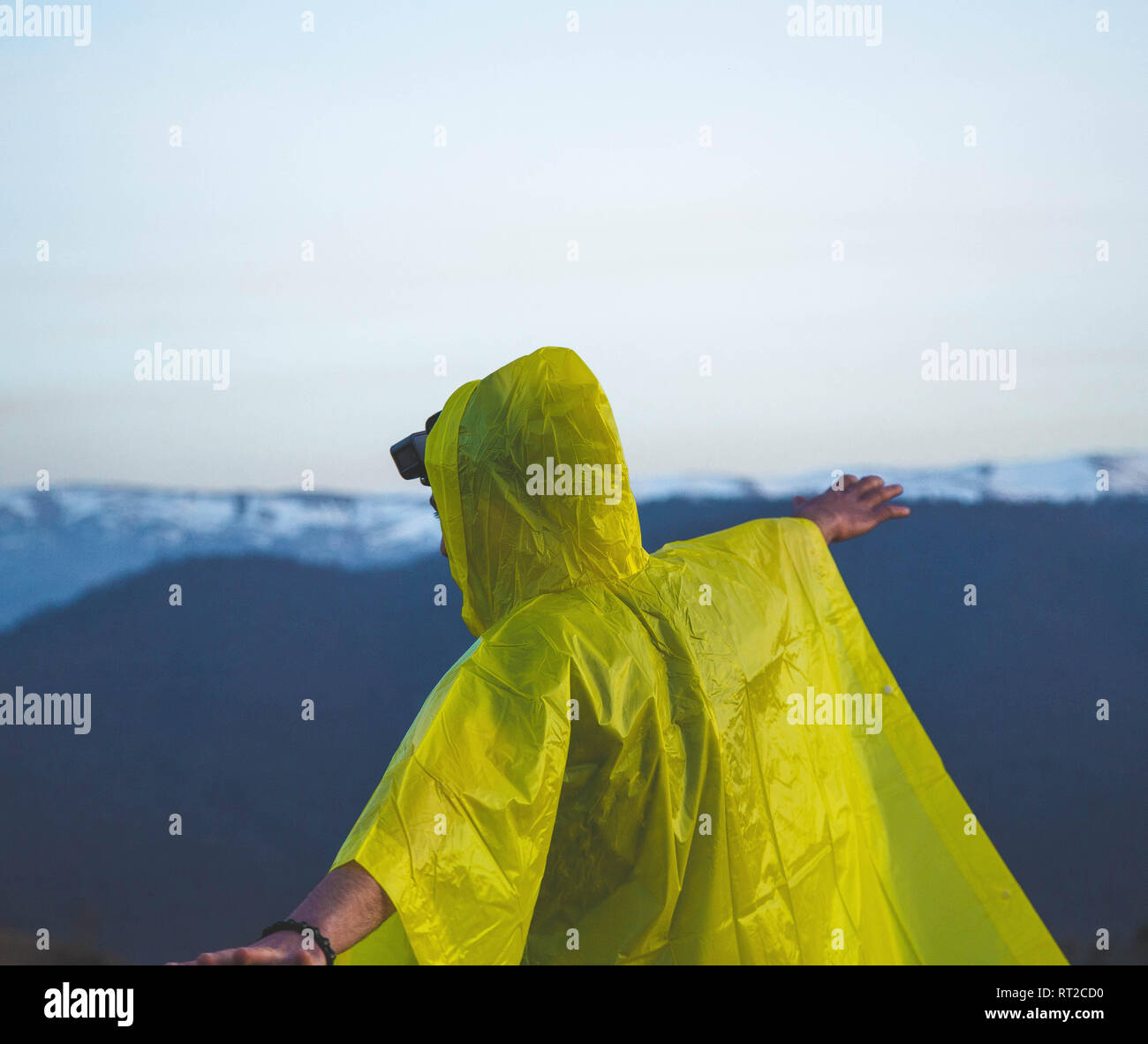 Mann in einem Regenmantel genießen den Regen auf einem Hügel Stockbild