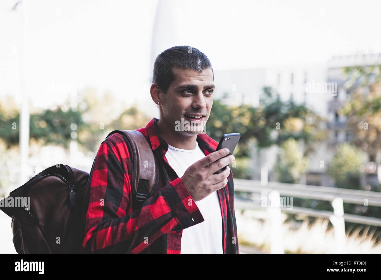 Junger Mann mit Rucksack und Handy unterwegs. Stockfoto