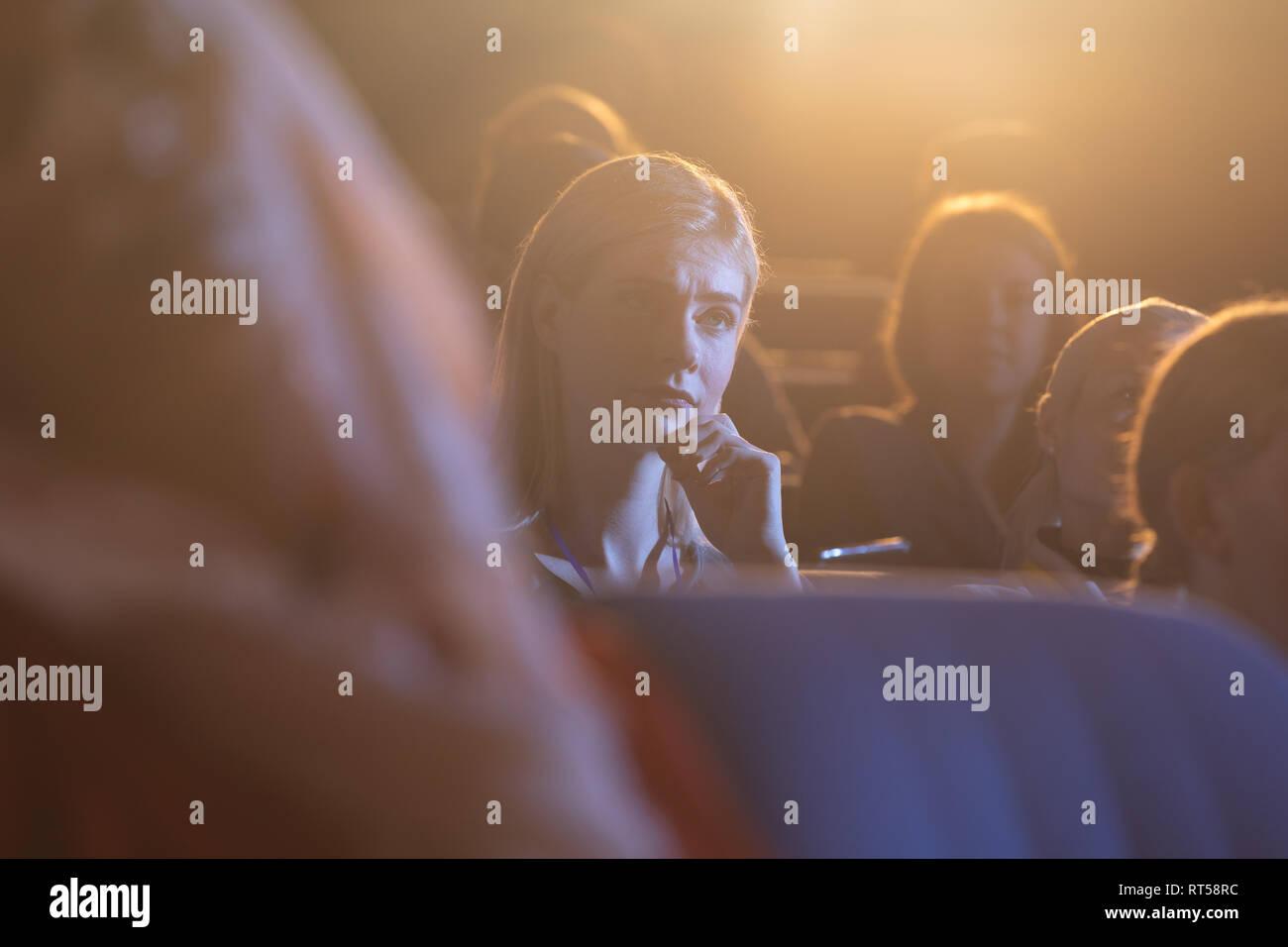Geschäftsfrau sitzen und hören auf die Präsentation mit Konzentration im Auditorium Stockbild