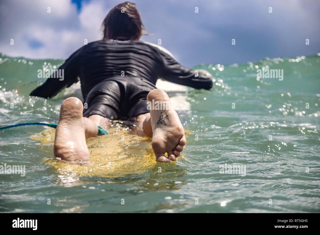 Indonesien, Bali, Kuta, Surfer liegen auf Surfbrett, Tattoo auf der Fußsohle Stockfoto