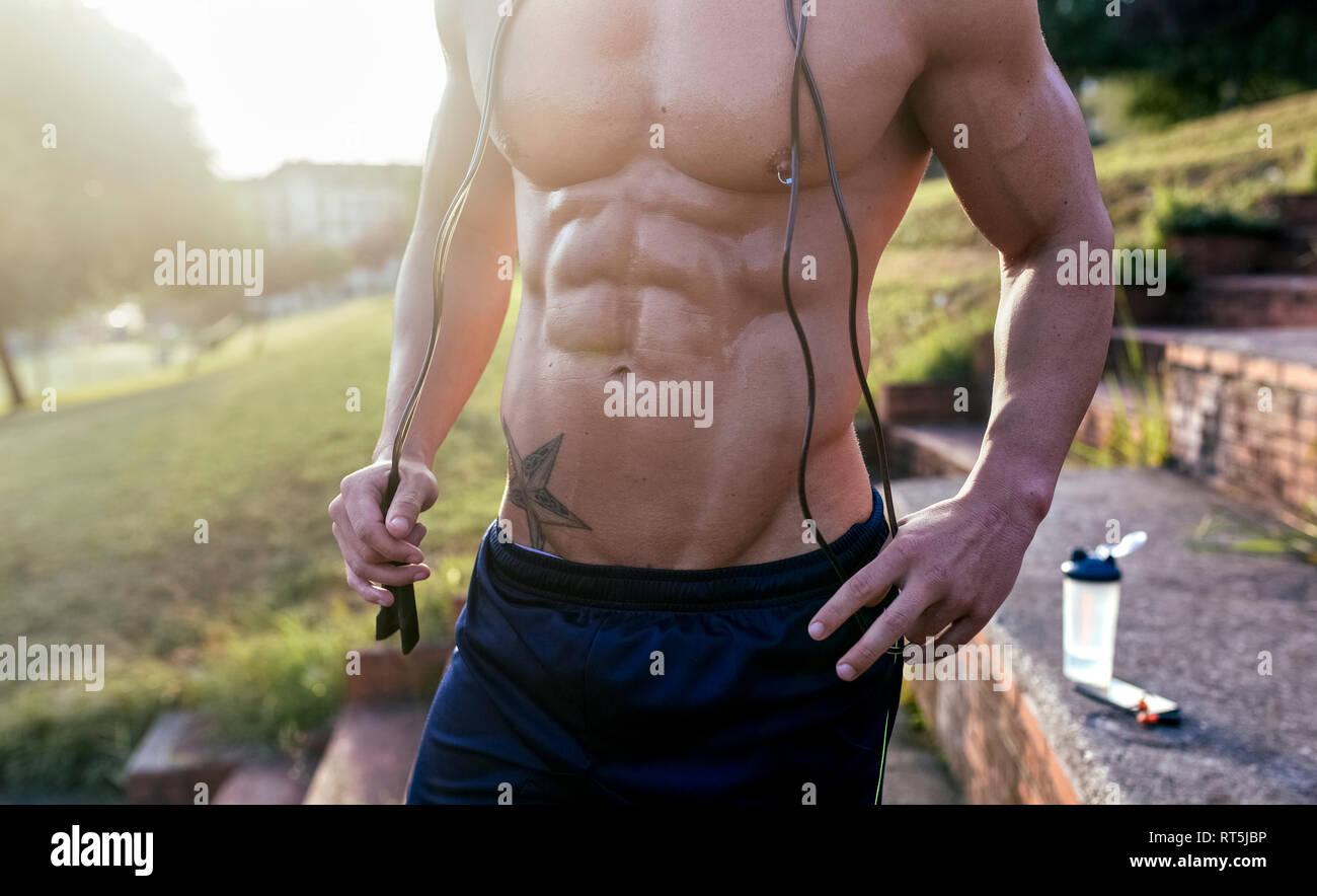 Im mittleren Abschnitt der barechested muskulösen Mann mit Springseil im Freien Stockbild
