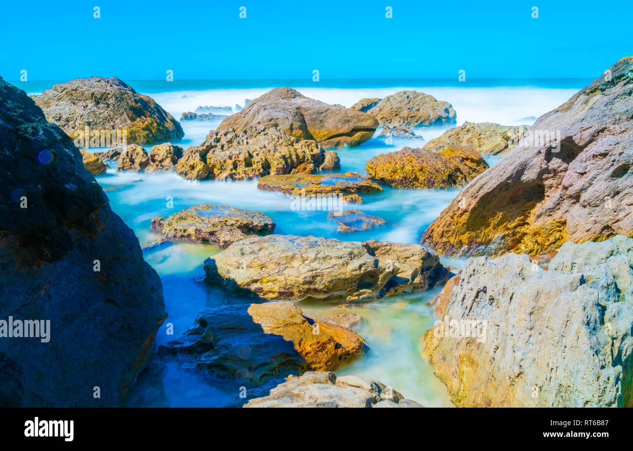 Wellen, die durch lange Belichtung waschen in Um felsige Küste, an der Basis der Mount Maunganui Tauranga, Neuseeland geglättet Stockfoto