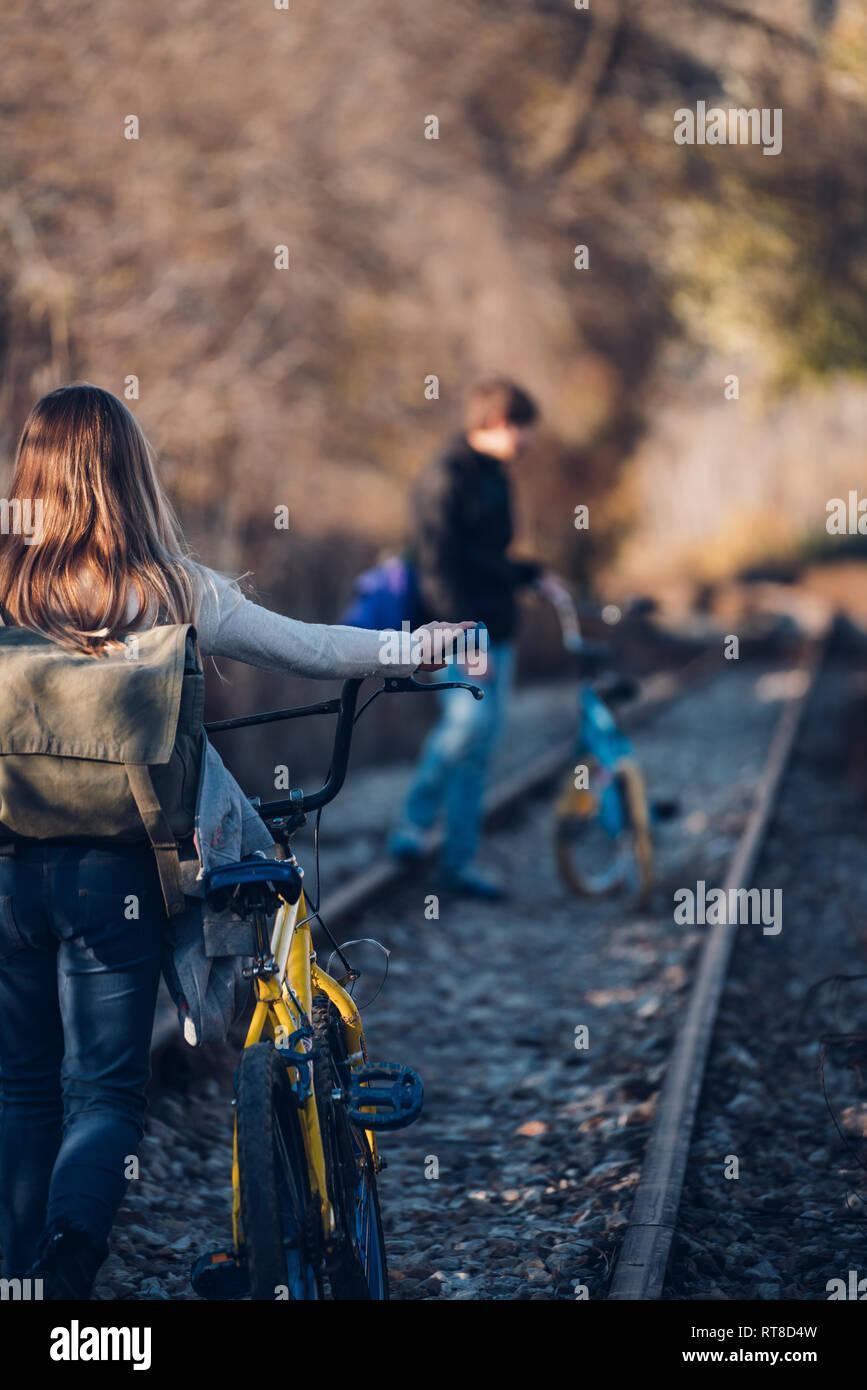 Junge und Mädchen zu Fuß auf der Bahn mit Fahrrädern Stockfoto