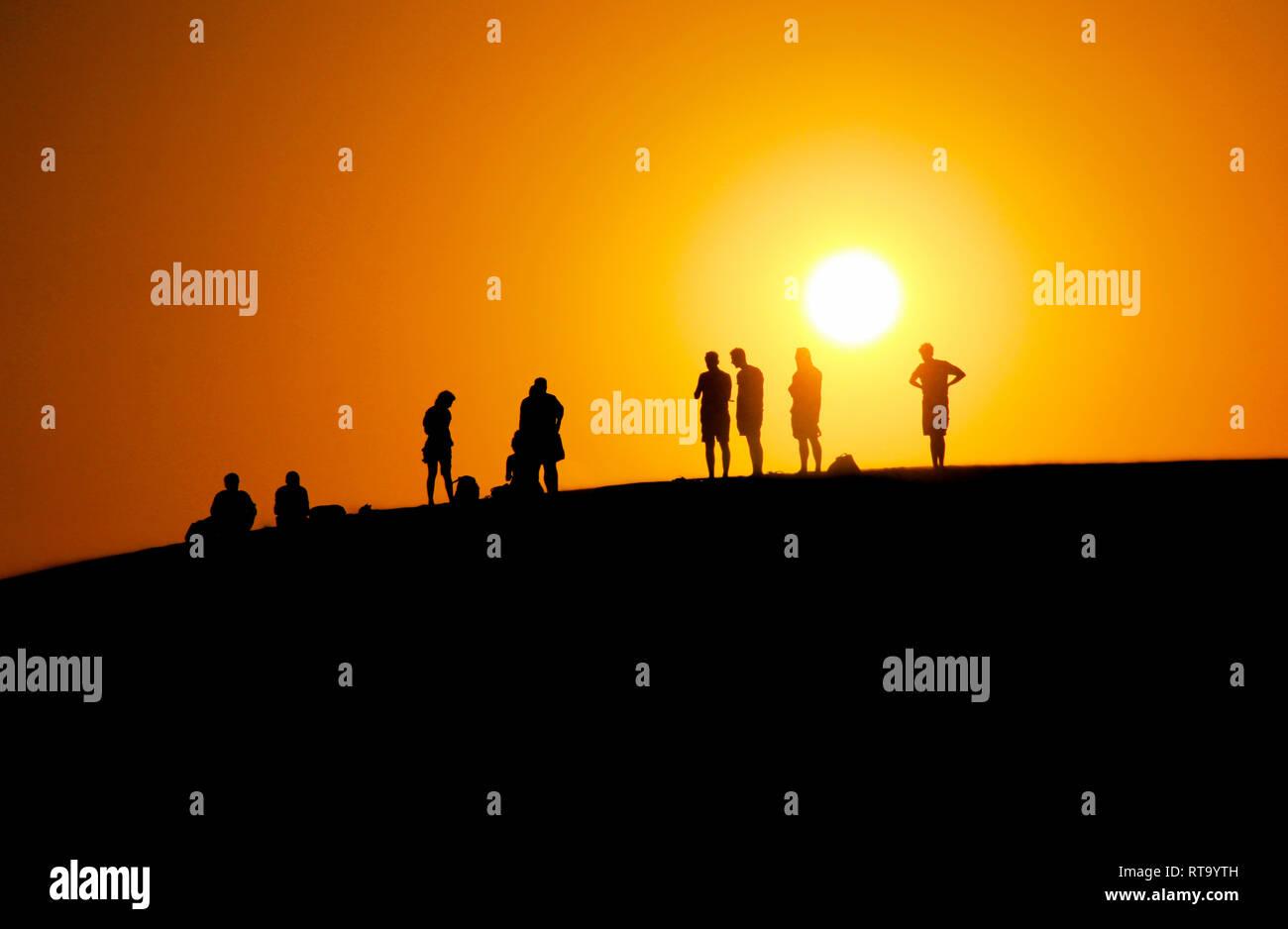 Ein schönes Bild von Menschen warten auf den Sonnenuntergang am Rand der Düne (Rot Sand dune) mit orange Himmel Hintergrund im Sommer in Mui Ne, Vietnam Stockfoto