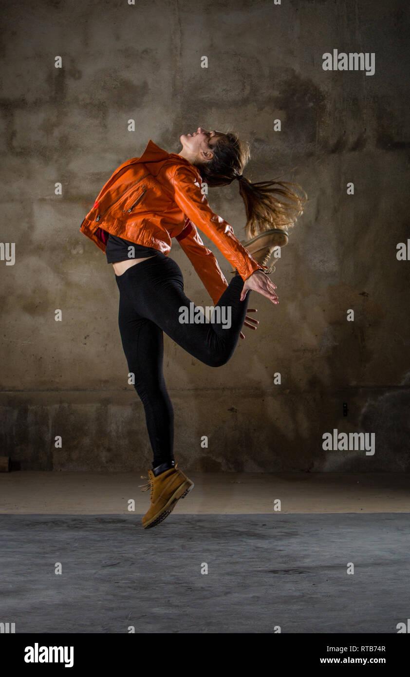 Seitenansicht der jungen Dame in Freizeitkleidung springen mit Bein gestreckt in Grau düsteren Zimmer zurück Stockbild
