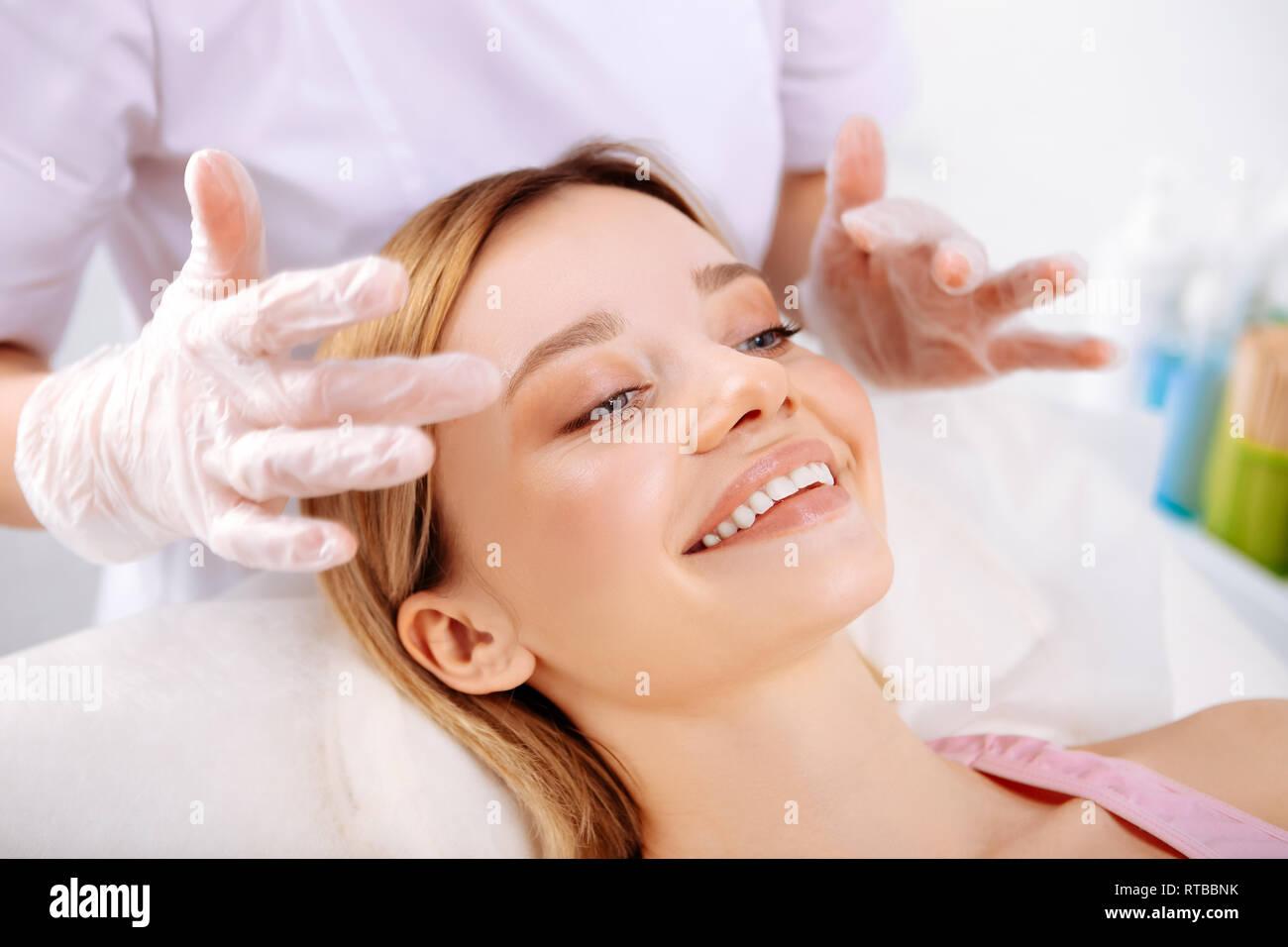 Kosmetiker, Gesichtsmassage, wunderschönen Lächeln client Stockbild