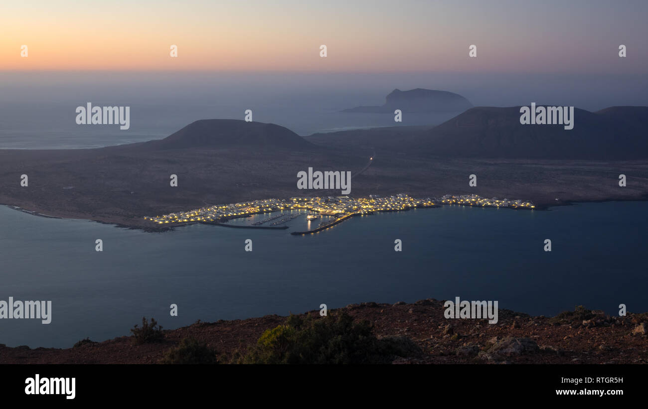 Blick vom Mirador del Rio auf Lanzarote bei Sonnenuntergang mit der Insel La Graciosa. Kanaren Stockbild