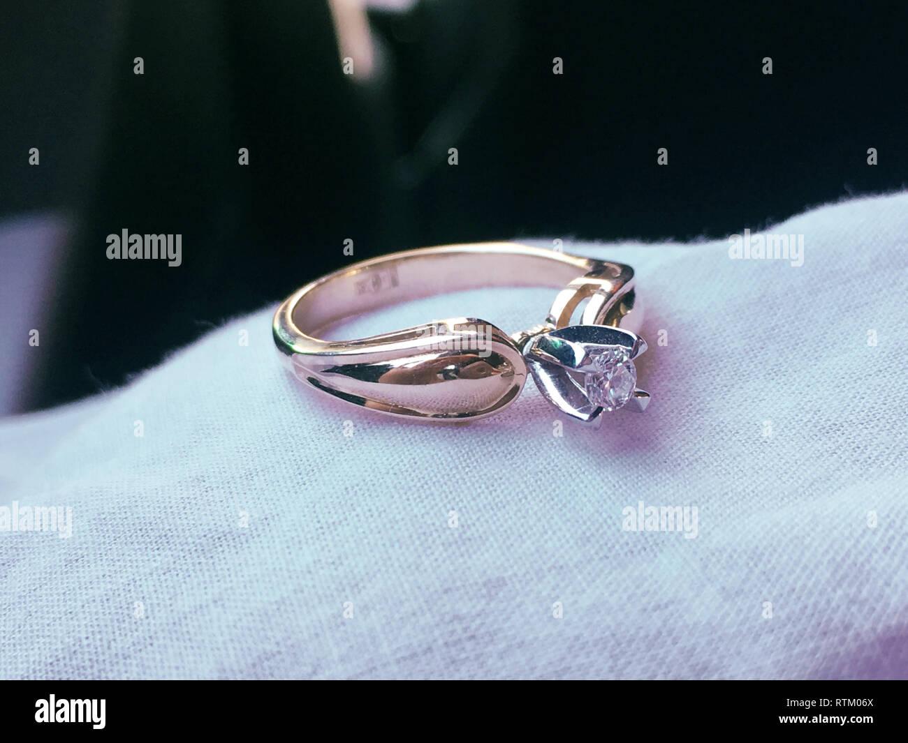 Nahaufnahme eines eleganten Diamond Ring auf dem Bett mit weißen und rosa getrocknete Blumen Bouquet Hintergrund, weiche und selektiven Fokus. Liebe und Hochzeit Konzept. Stockfoto