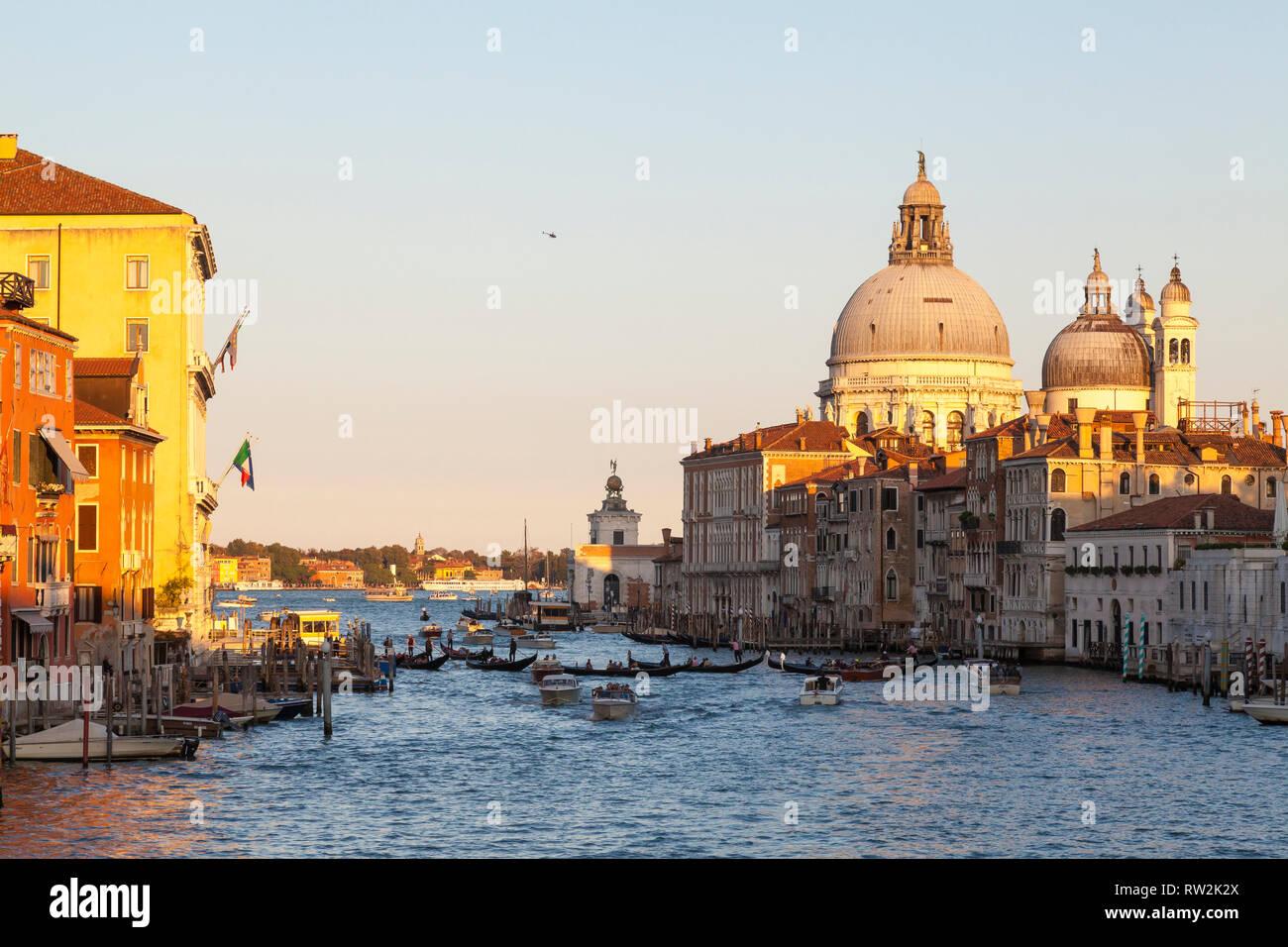 Sonnenuntergang auf den Canale Grande und die Basilica di Santa Maria della Salute, Venedig, Venetien, Italien mit mehreren Gondeln auf dem Canal und warmen goldenen Licht Stockfoto