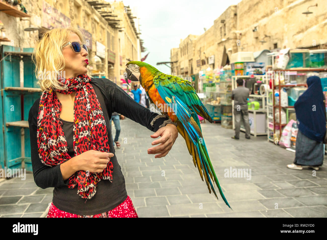 Glückliche Frau Küsse ein Papagei an Vogel Souq in Souq Waqif, den alten Markt und Touristenattraktion in Al Souq, Doha City Centre, Katar Stockfoto