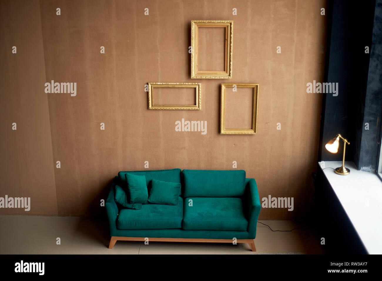 Emerald samt retro Sofa gegen einen warmen braunen Wand. Das Innere eines stilvollen Zimmer. Leere gold Frames an der Wand. Stockfoto