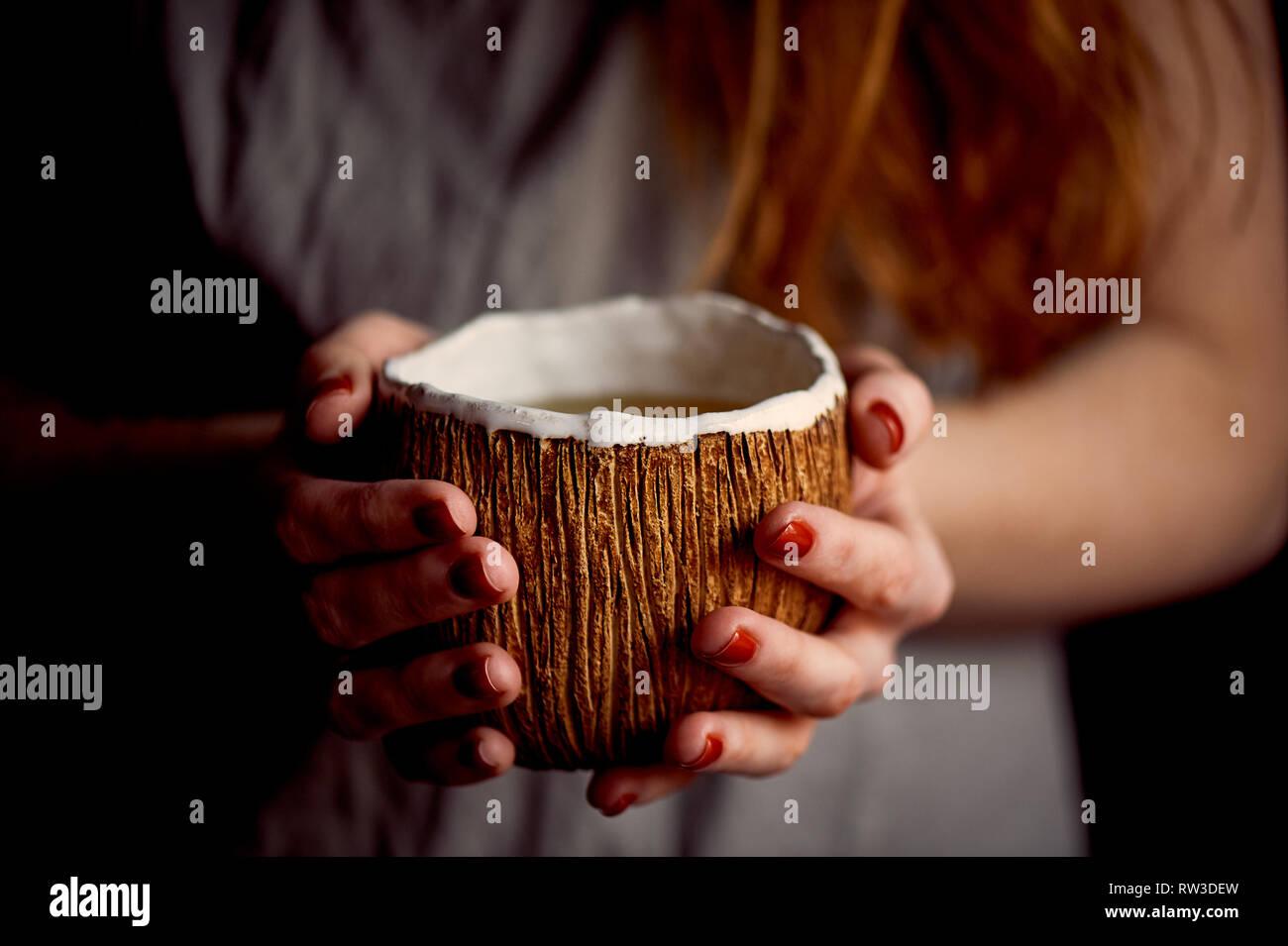 Rothaarige Mädchen mit einem dampfenden Getränke. Kaffee, Tee oder Kakao. Handgefertigte Keramik Stockbild