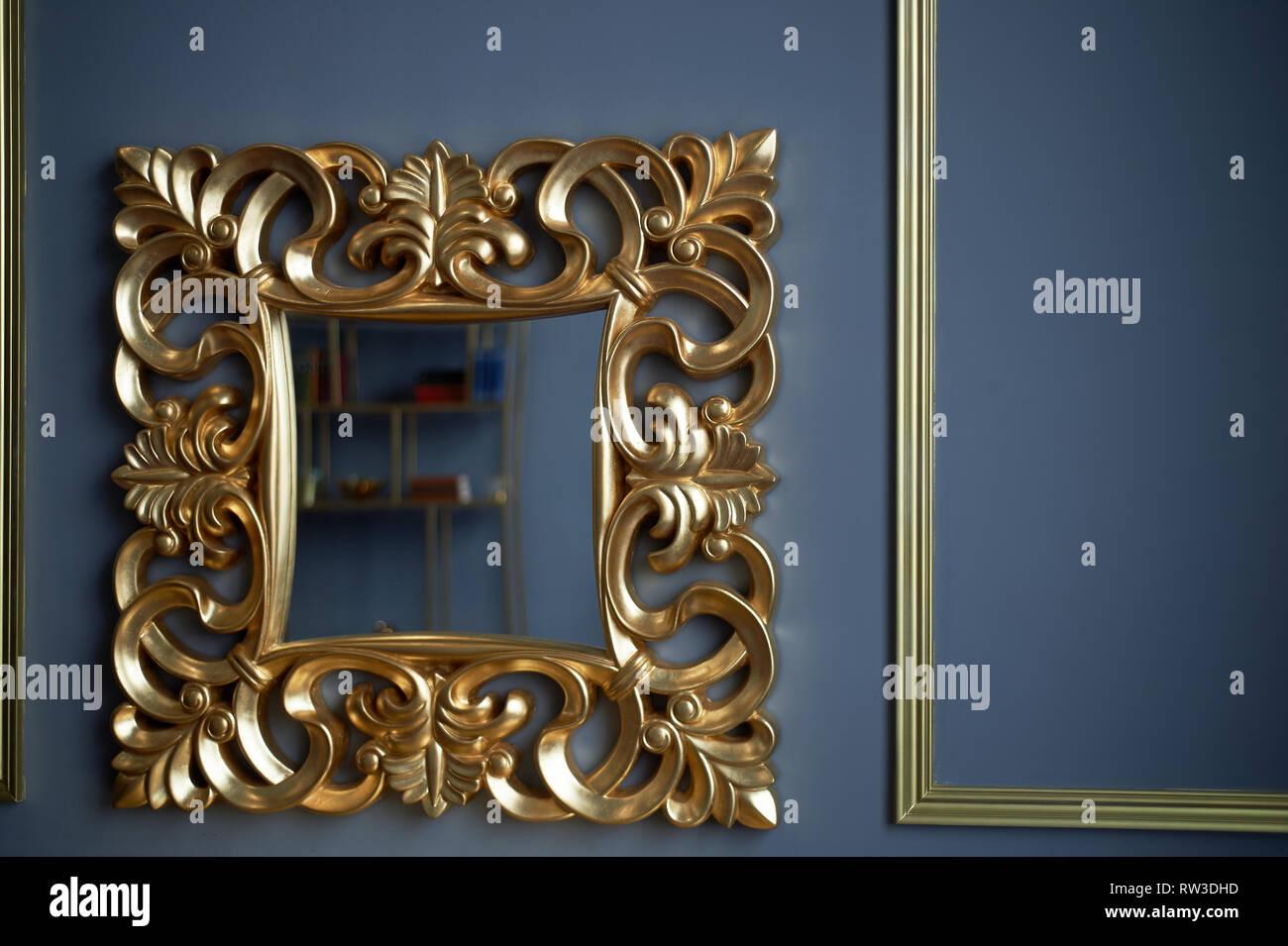 Spiegel in einer goldenen Maßwerk Frame auf dem Hintergrund der klassischen grauen Wänden Stockbild