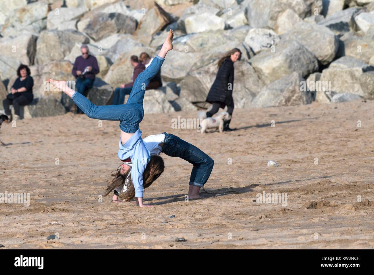Junge energische Mädchen im Teenageralter, Handstand auf den Fistral Beach in Newquay Cornwall. Stockbild