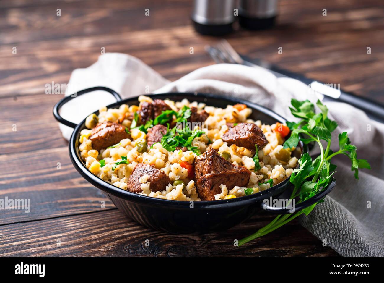 Bulgur mit Fleisch und Gemüse auf hölzernen Tisch Stockfoto