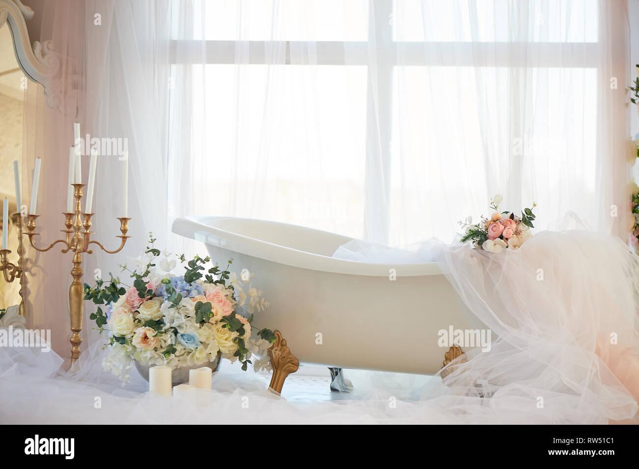 Badewanne auf Golden Lion's Pfoten. Die Atmosphäre von Romantik und Liebe. Helle Einrichtung, Chiffon, Blumen. Stockbild