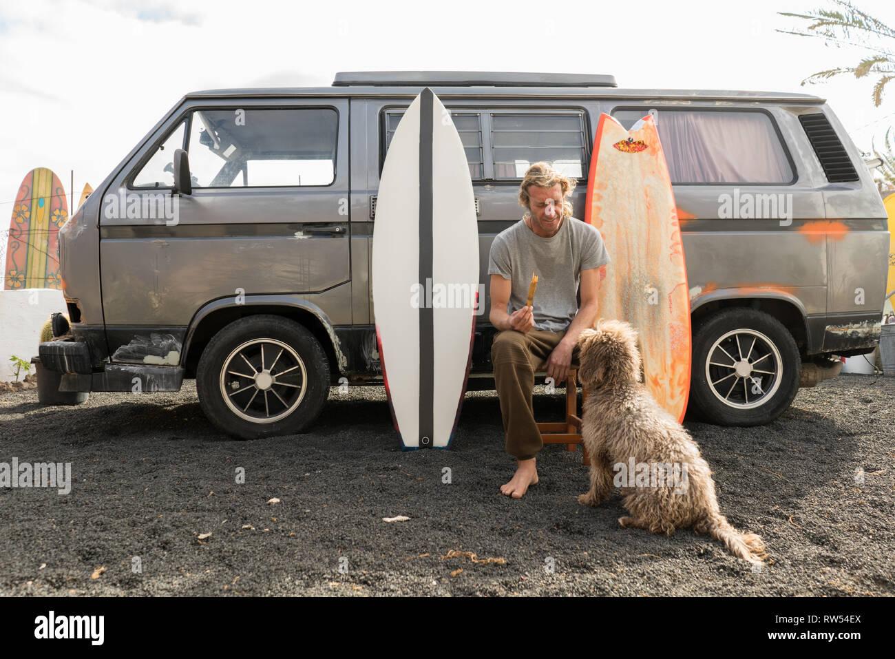 Mann stand in der Nähe von Surf Boards und Van Stockbild