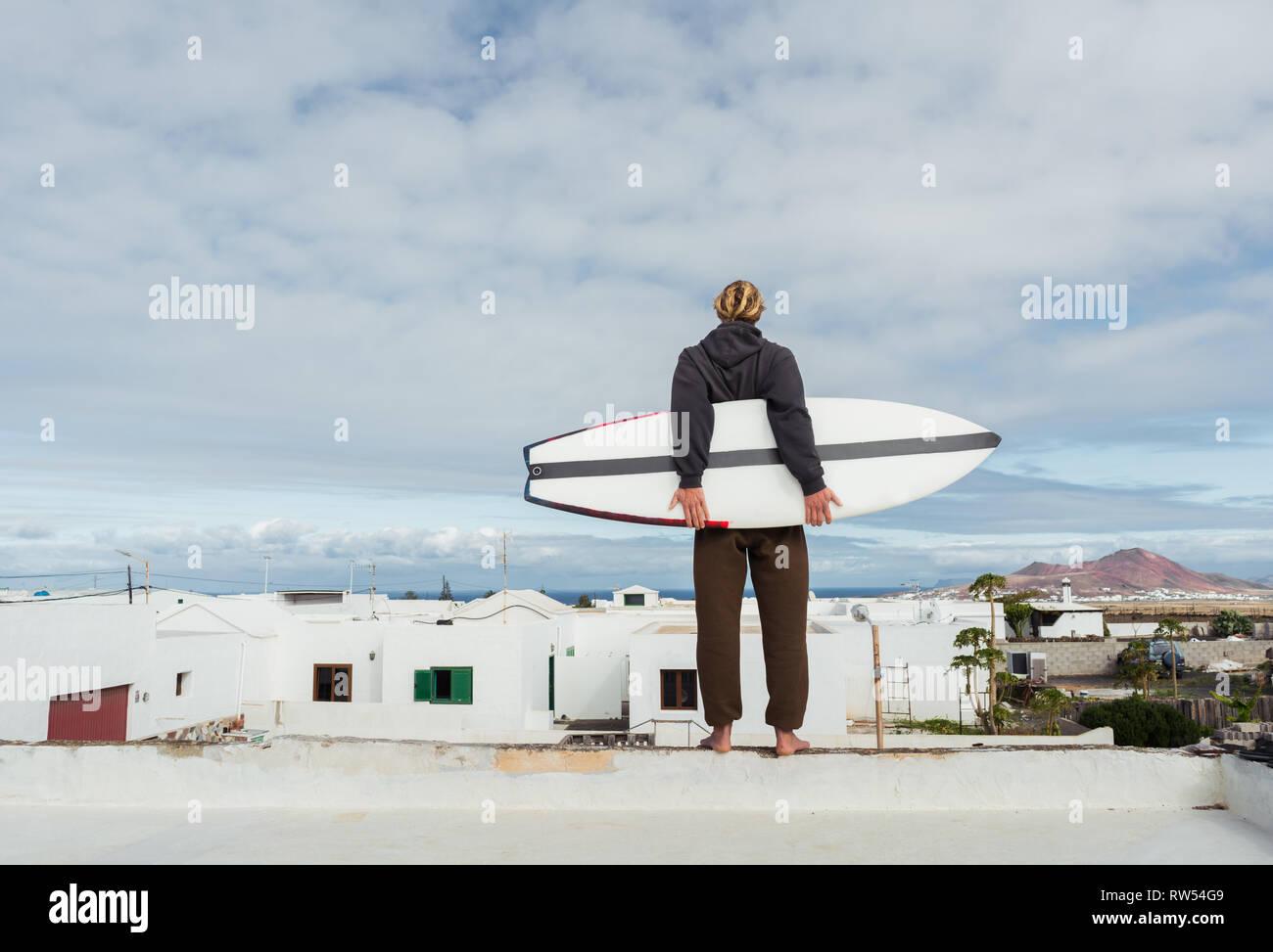 Mann mit Surfbrett auf dem Dach von Gebäude und Blick auf die Berge Stockbild