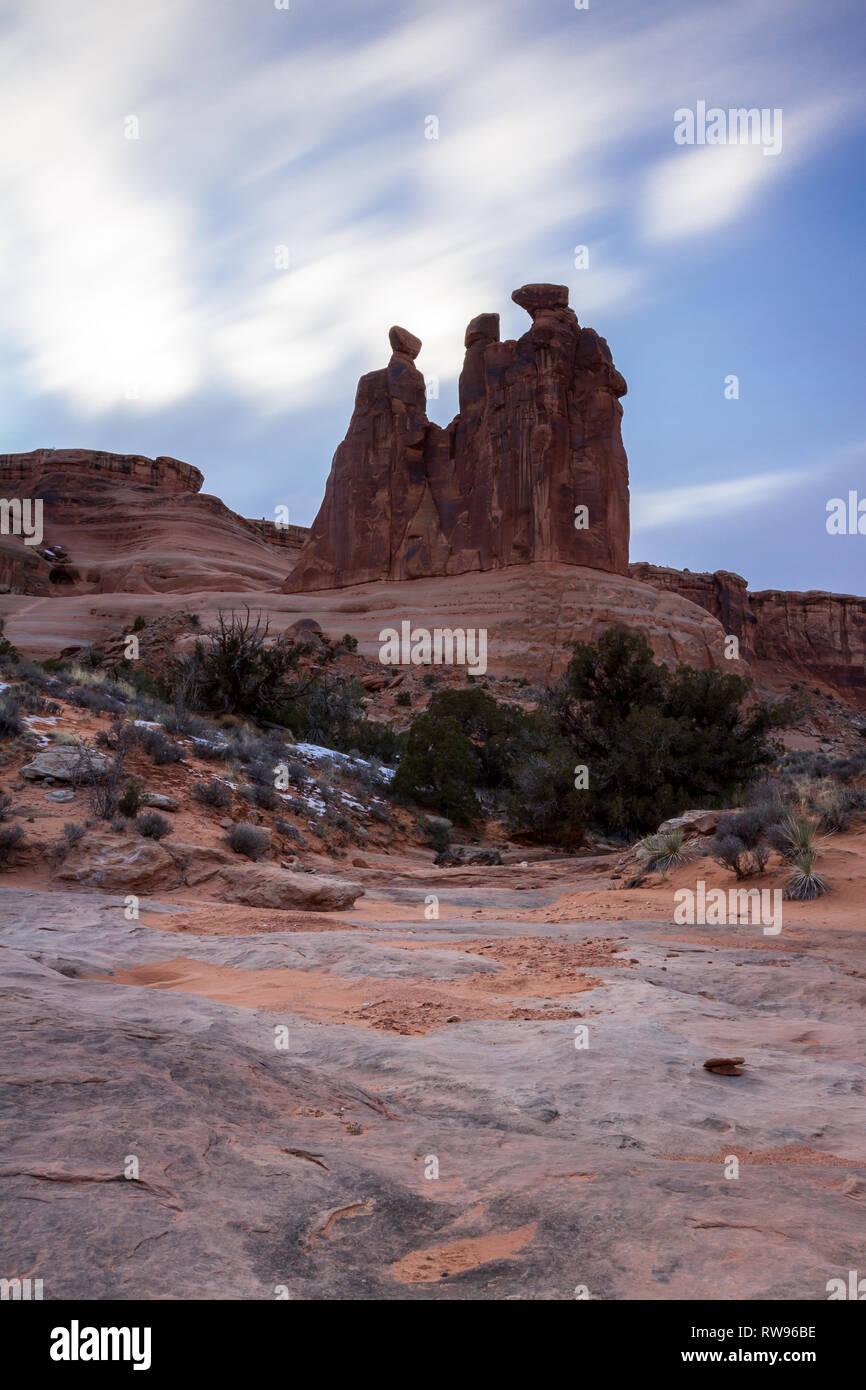 Giant Red Rock verfügen als die Drei Klatschbasen im Arches National Park, Foto takin mit einer sehr langsamen shuttterpeed das sich schnell bewegende Wolken zu verwischen bekannt Stockfoto