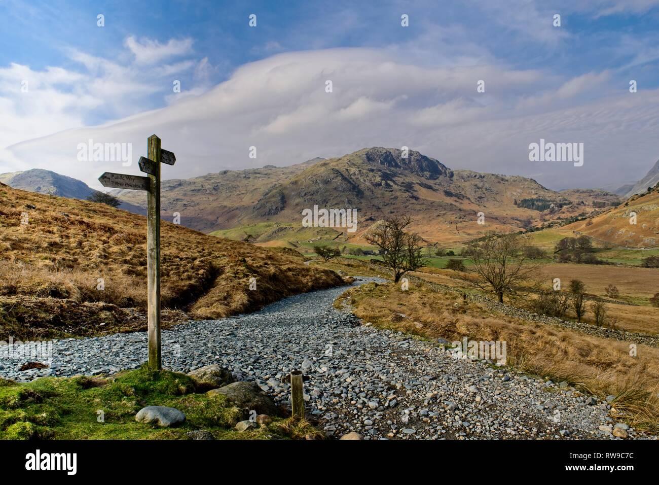 Eine fingerpost an einer Kreuzung der Wege im Little Langdale mit Hecht O'Blisco im Hintergrund Stockfoto