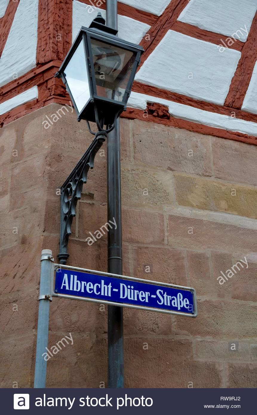 Blau metallic Straßenschild über Albrecht Dürer Straße (street), ein mittelalterliches Fachwerk Haus aus Stein, Nürnberg, Deutschland, ein nostalgischer Straße Stockbild