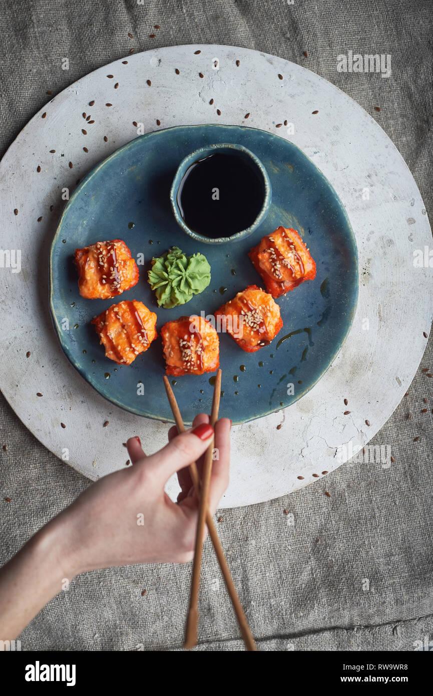 Traditionelle japanische Küche auf handgefertigte Keramik. Gebackene heißen Rollen auf einem blauen Ton Platte. Stockfoto