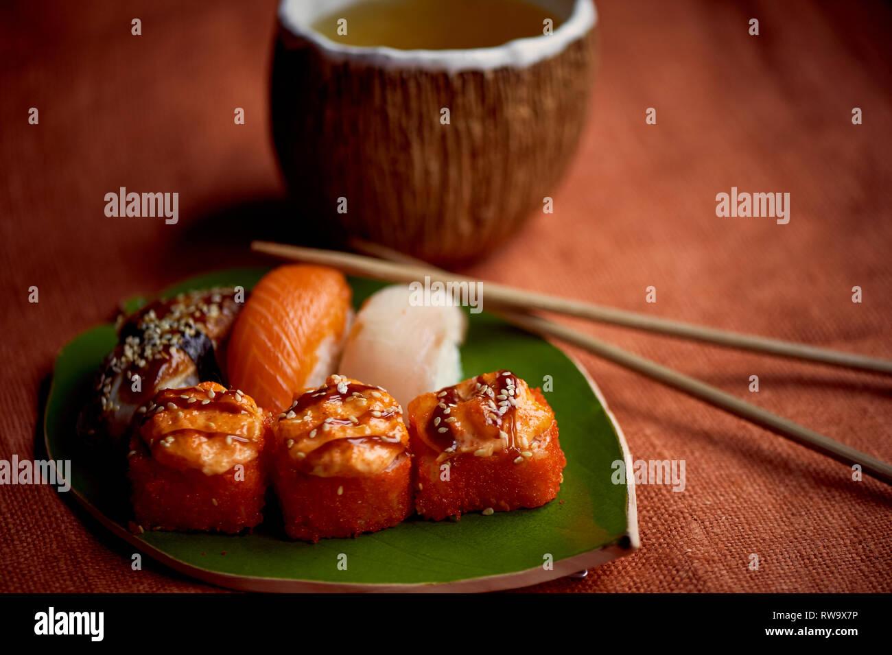 Traditionelle japanische Küche auf handgefertigte Keramik. in Form von Green leaf Platte, orange hinterlegt. Brötchen und Sushi. Stockbild