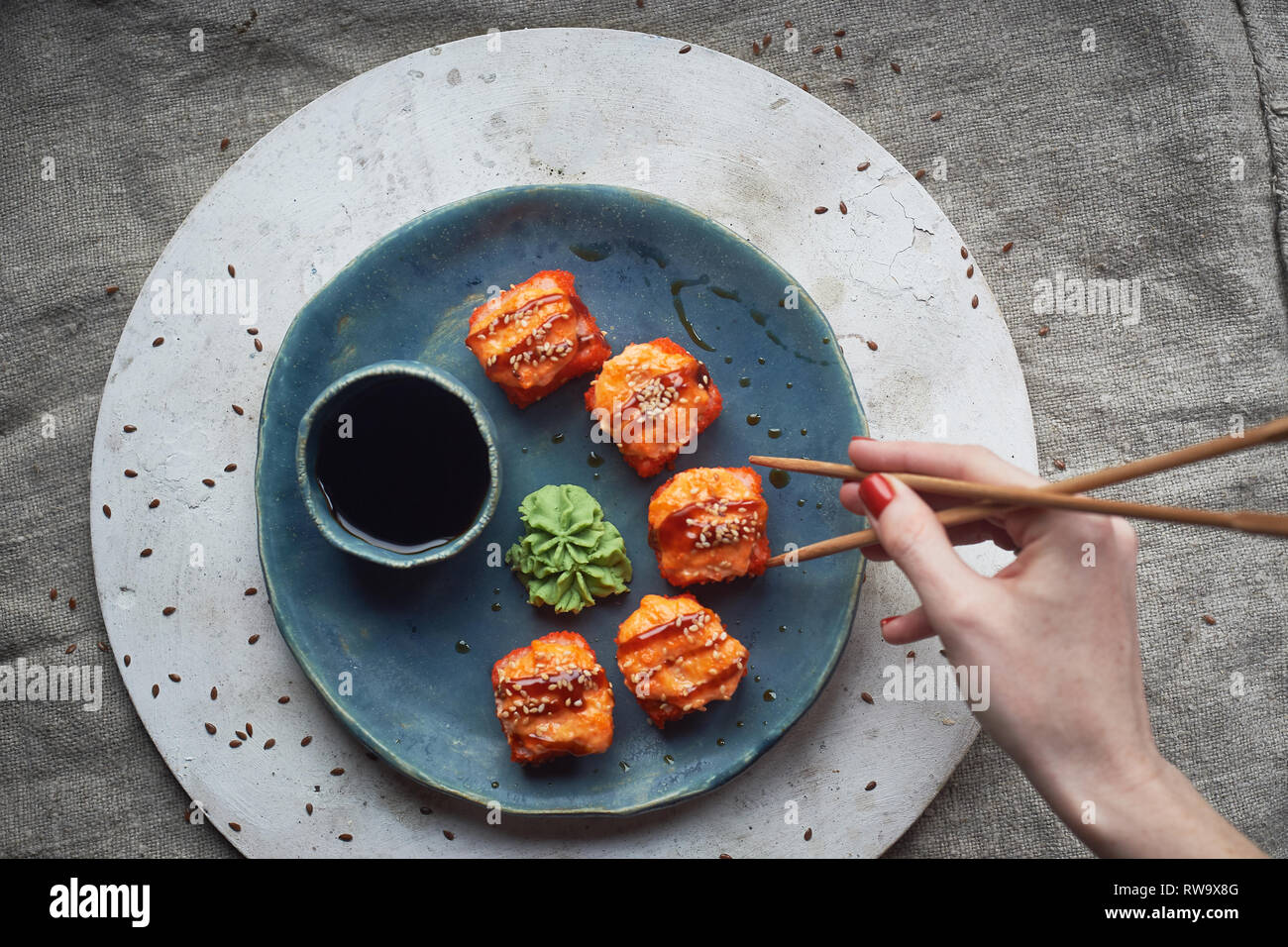 Traditionelle japanische Küche auf handgefertigte Keramik. Gebackene heißen Rollen auf einem blauen Ton Platte. Stockbild