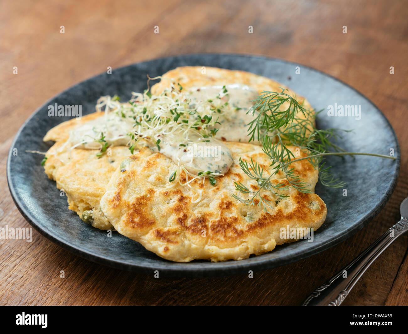Herzhafte vegane Erbse Pfannkuchen mit Schnittlauch und herbed Sauce. Stockbild