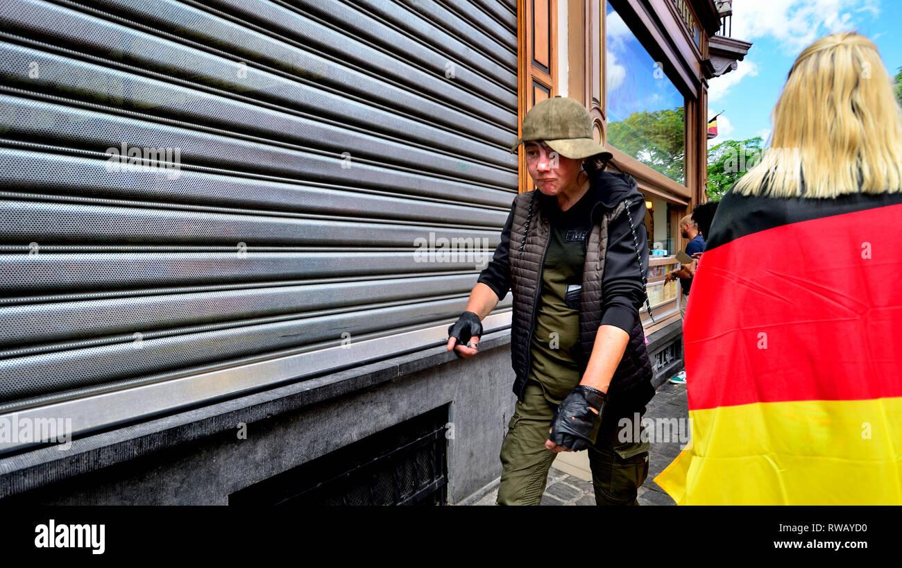Brüssel, Belgien. Frau auf der Straße vorbei gehen. Eine deutsche Flagge Stockbild