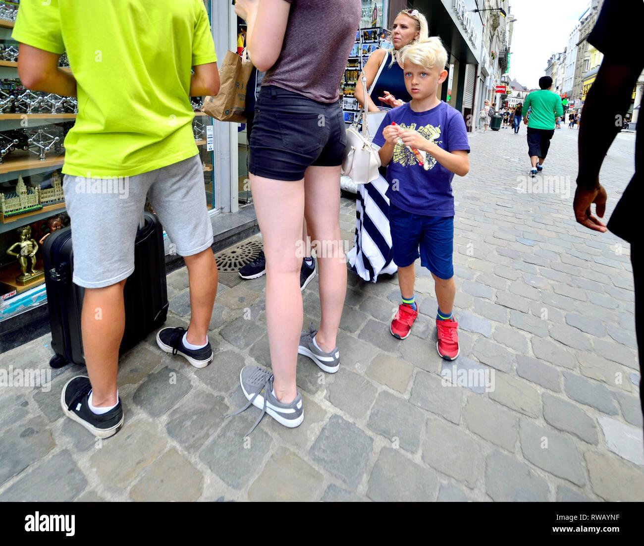 Brüssel, Belgien. Junge mit Familie außerhalb eines Shop Stockbild