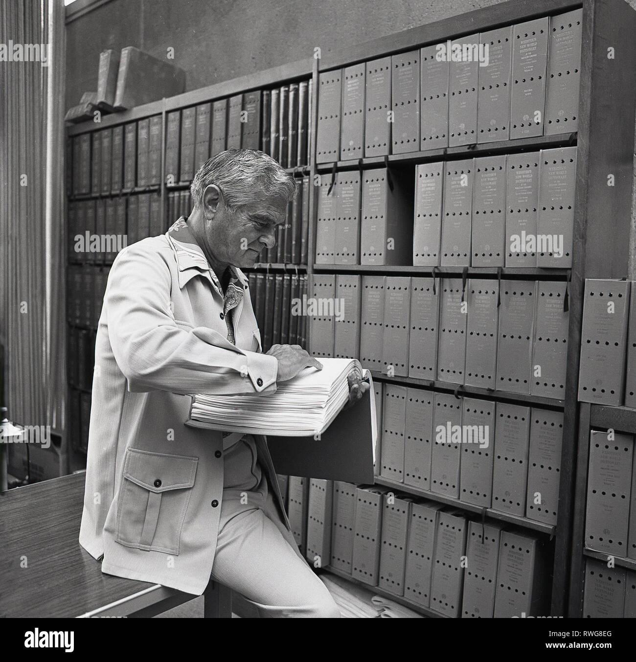 1970 s, Mann in einer Präsenzbibliothek, etwas das in der Neuen Welt ein Webster Wörterbuch der amerikanischen Langague, Los Angeles, USA. Das Wörterbuch wurde erstmals im Jahr 1951 und einer seiner bemerkenswerten Features veröffentlicht wurde seine volle Etymologie, die Herkunft und Entwicklung der Wörter. Stockbild