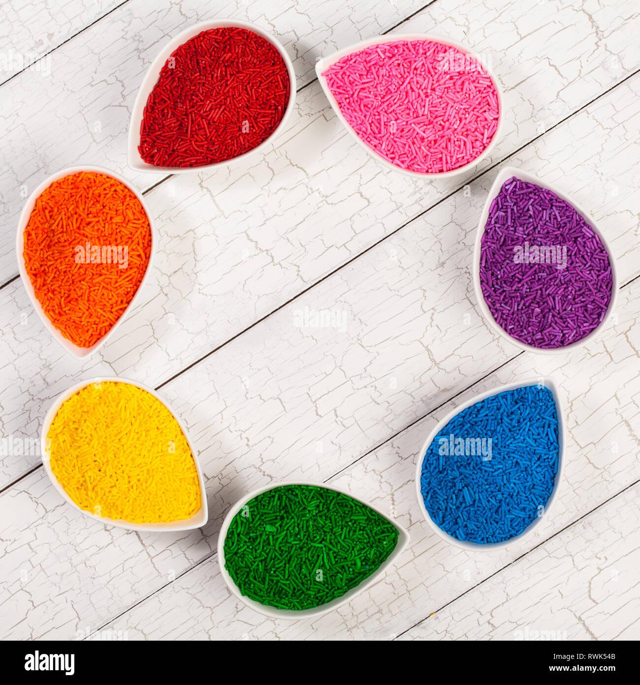 Ein Regenbogen Sortiment von bunten Streuseln Backen zum Dekorieren Kekse und Kuchen in Blütenblatt benutzt geformte Schüsseln Stockfoto
