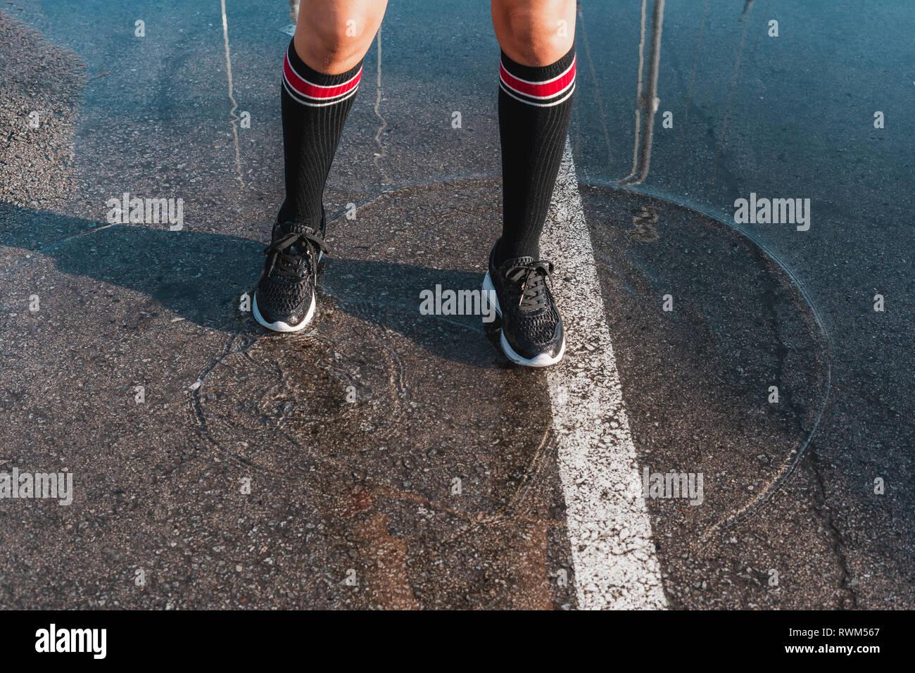 Von oben crop Beine der jungen Dame in Beinlinge und Jogging Schuhe stehen im Wasser slops auf Asphalt Stockbild