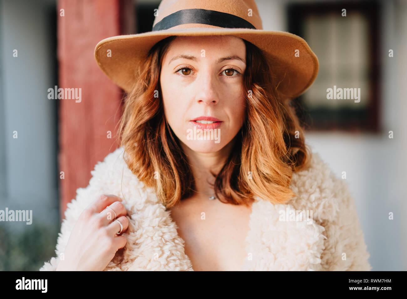 Positive attraktive junge Dame in warmen Verschleiß und Hut an Kamera suchen Stockbild