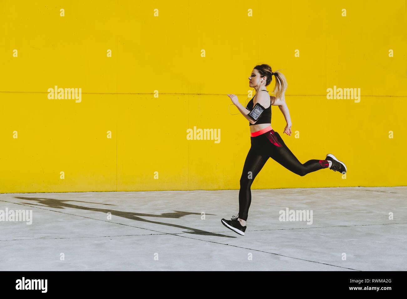 Seitenansicht der jungen Dame in Sportswear mit Kopfhörer läuft in der Nähe von Yellow Wall im sonnigen Tag Stockbild