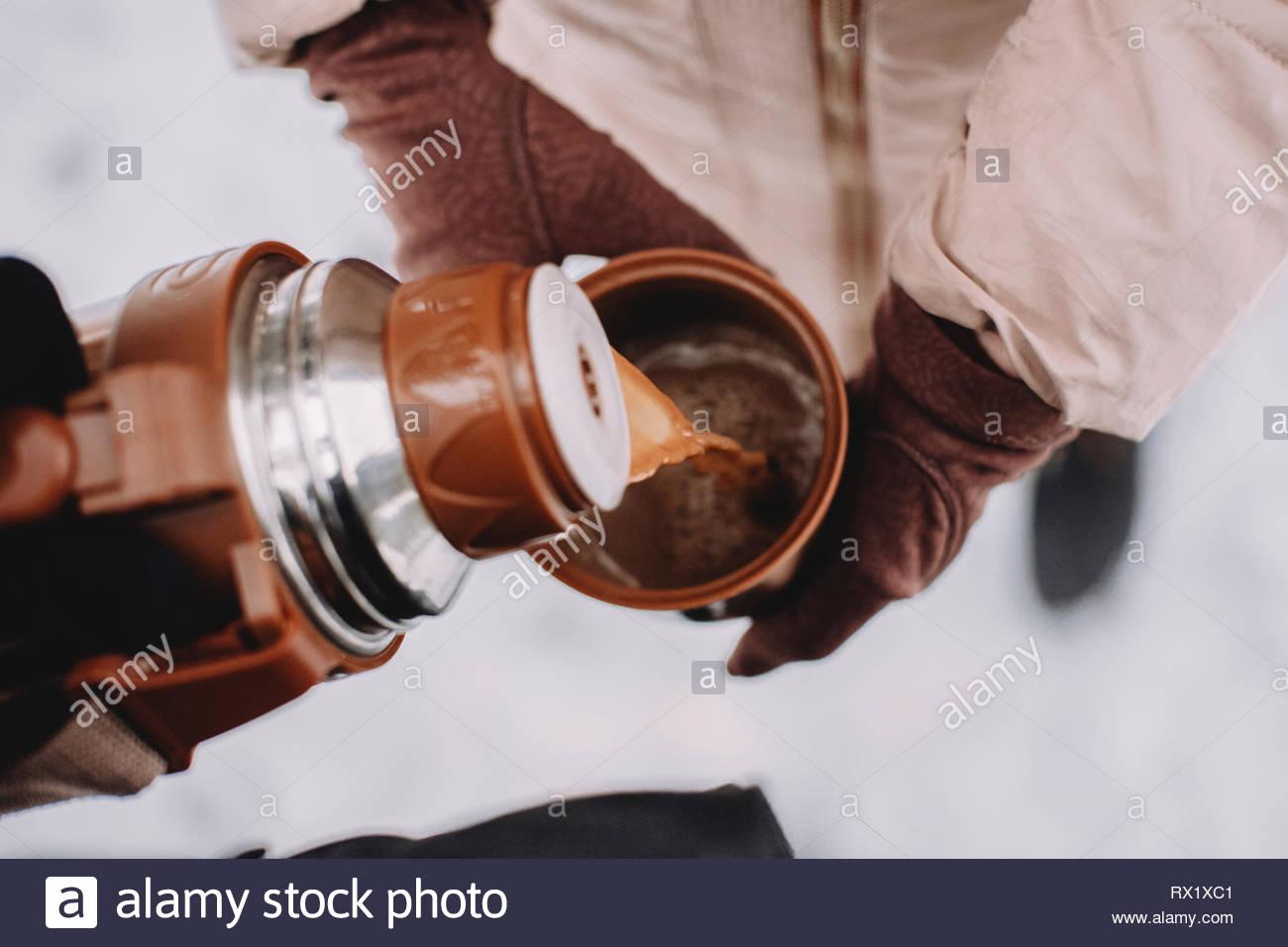 7/8 Hand von Frau gießen Kaffee für Frau in Schale an der Park im Winter Stockbild