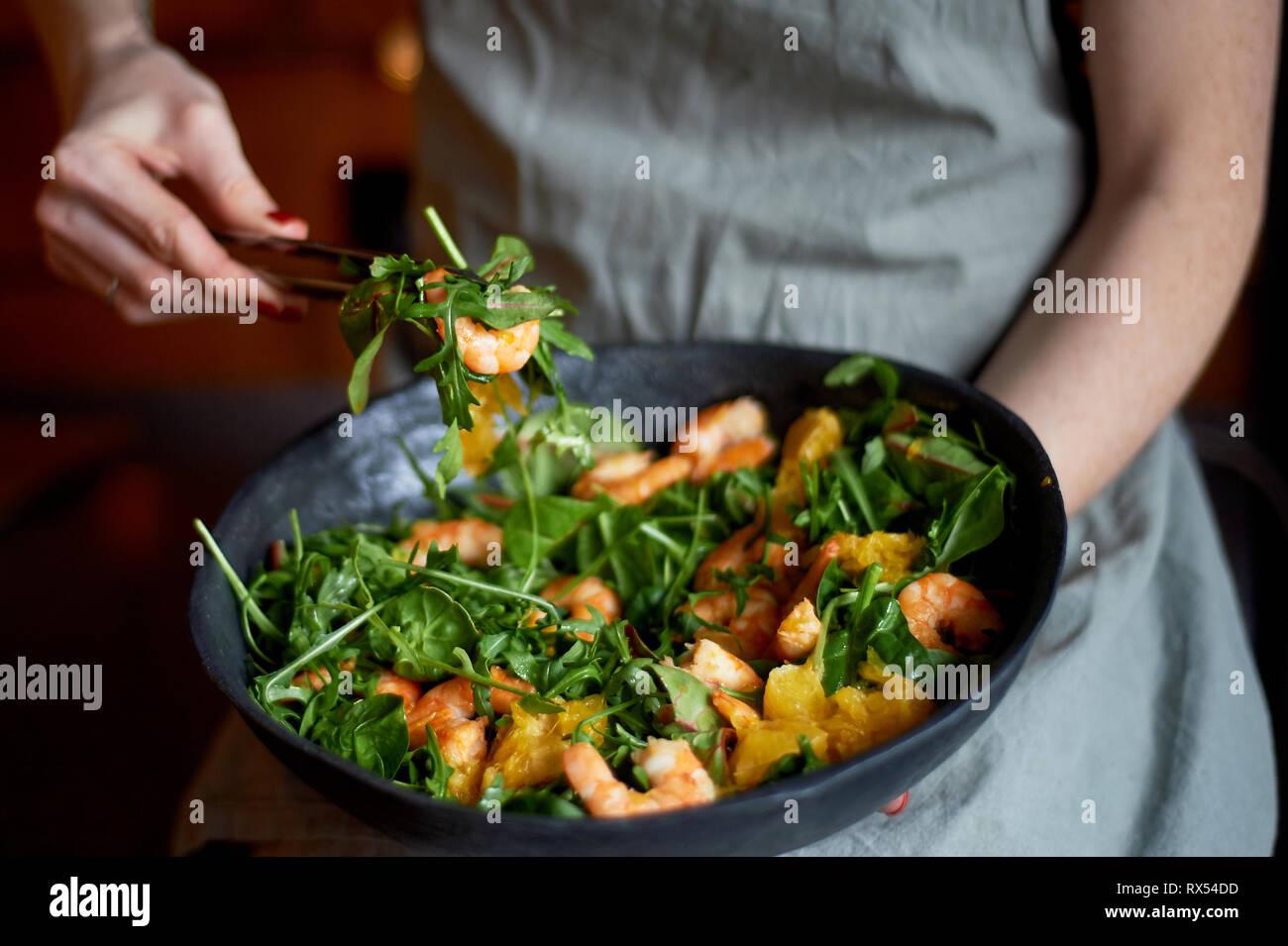 Gesunde Ernährung. Salat mit Rucola, Riesengarnelen und Orangen. Licht Gericht mit Meeresfrüchten. Diätmenü. Hände Salat stören Stockbild