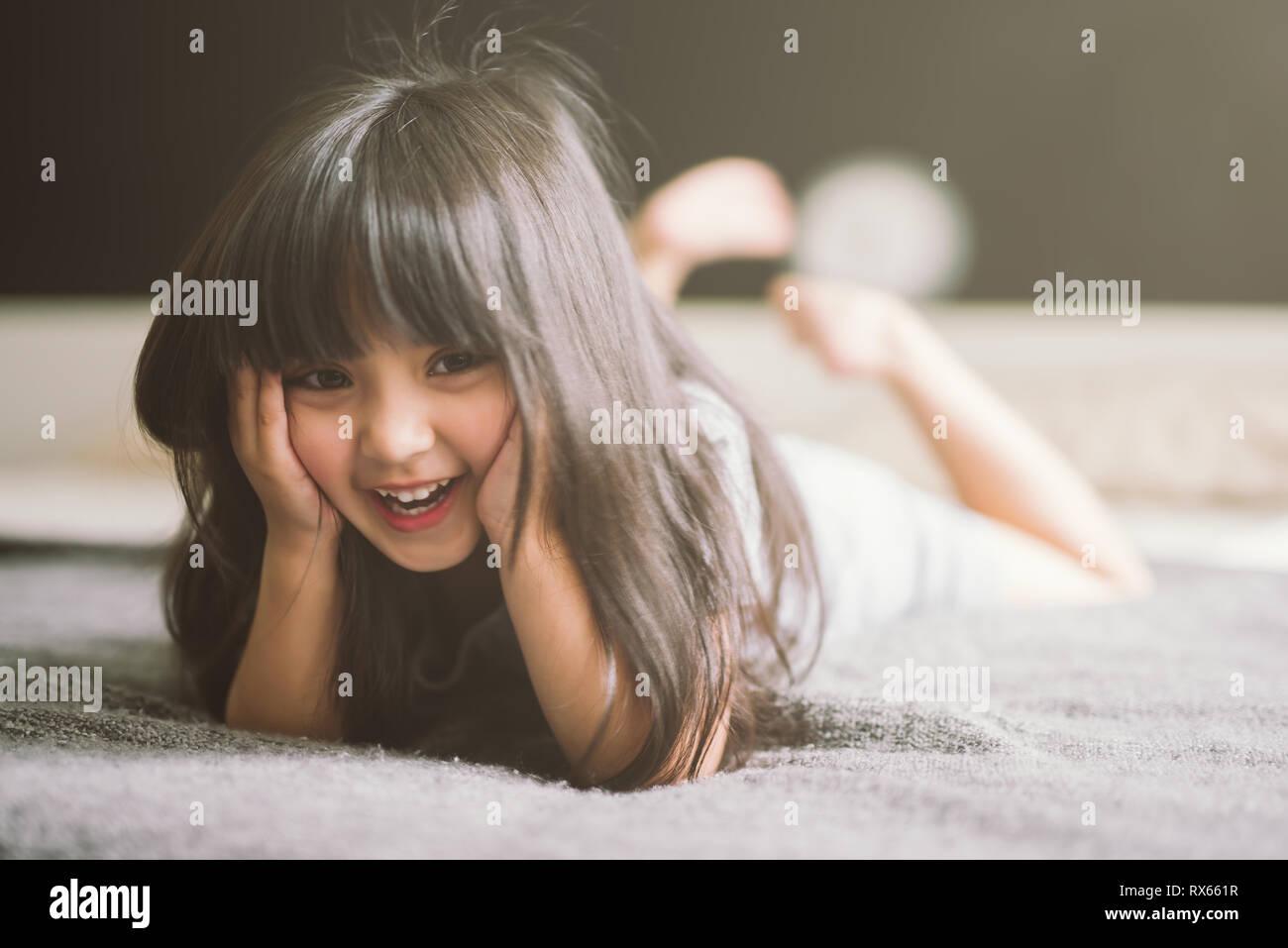 Glückliche kleine Mädchen mit auf dem Bett Stockfoto